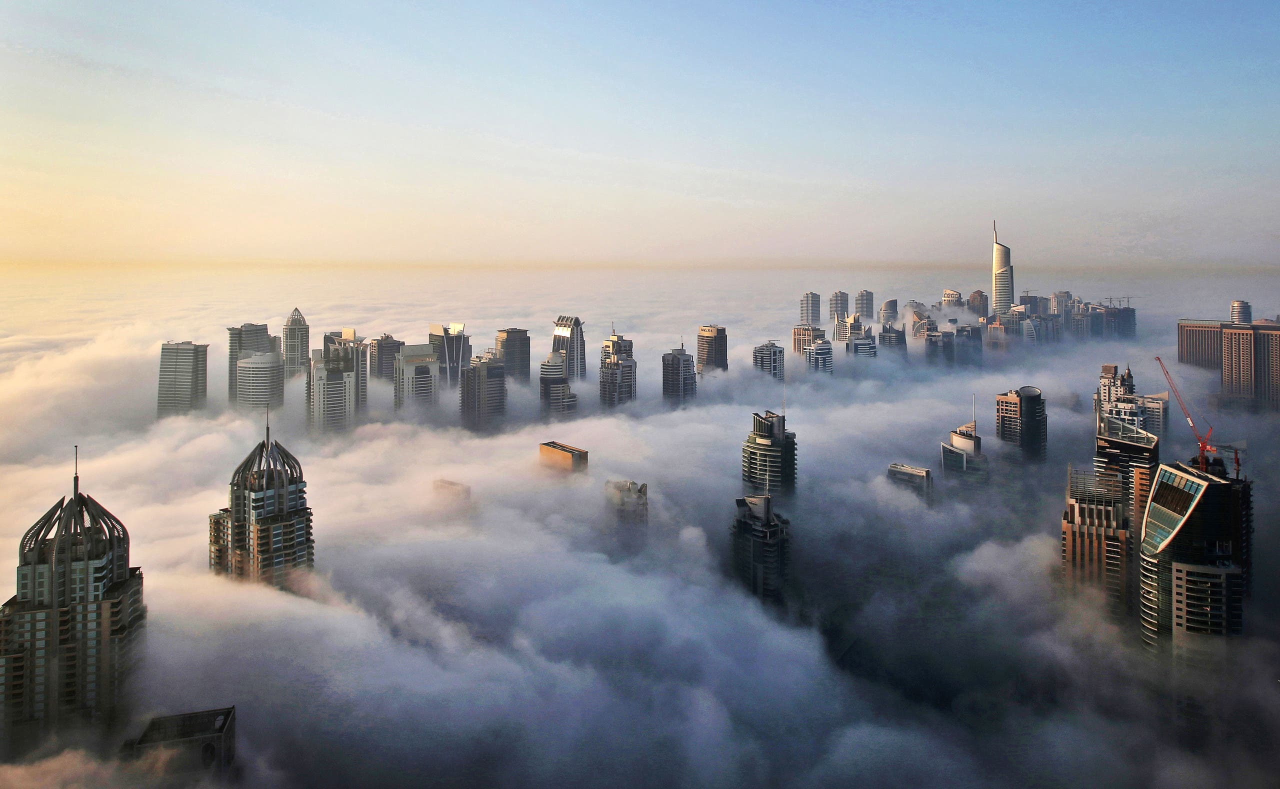 In this Monday, Oct. 5, 2015 photo, a thick blanket of early morning fog partially shrouds the skyscrapers of the Marina and Jumeirah Lake Towers districts of Dubai, United Arab Emirates. (AP)