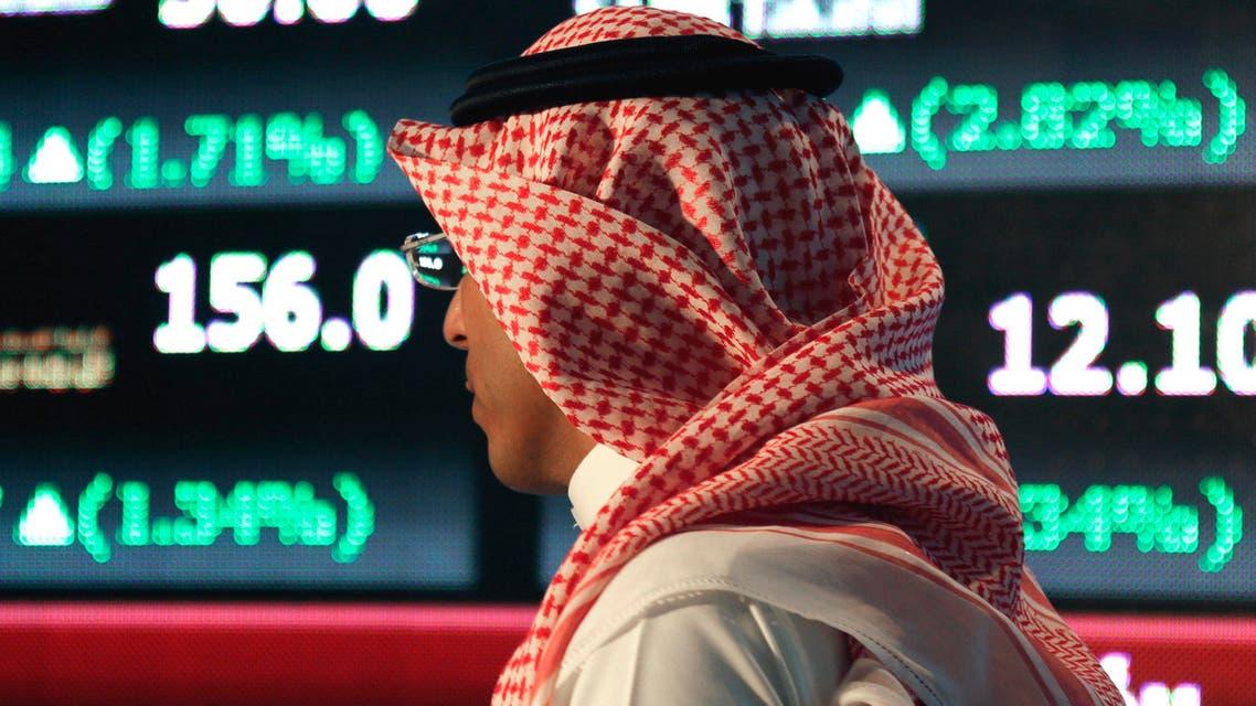 In this Monday, June 15, 2015 file photo, a Saudi man walks at the Tadawul Saudi Stock Exchange, in Riyadh, Saudi Arabia. (AP)