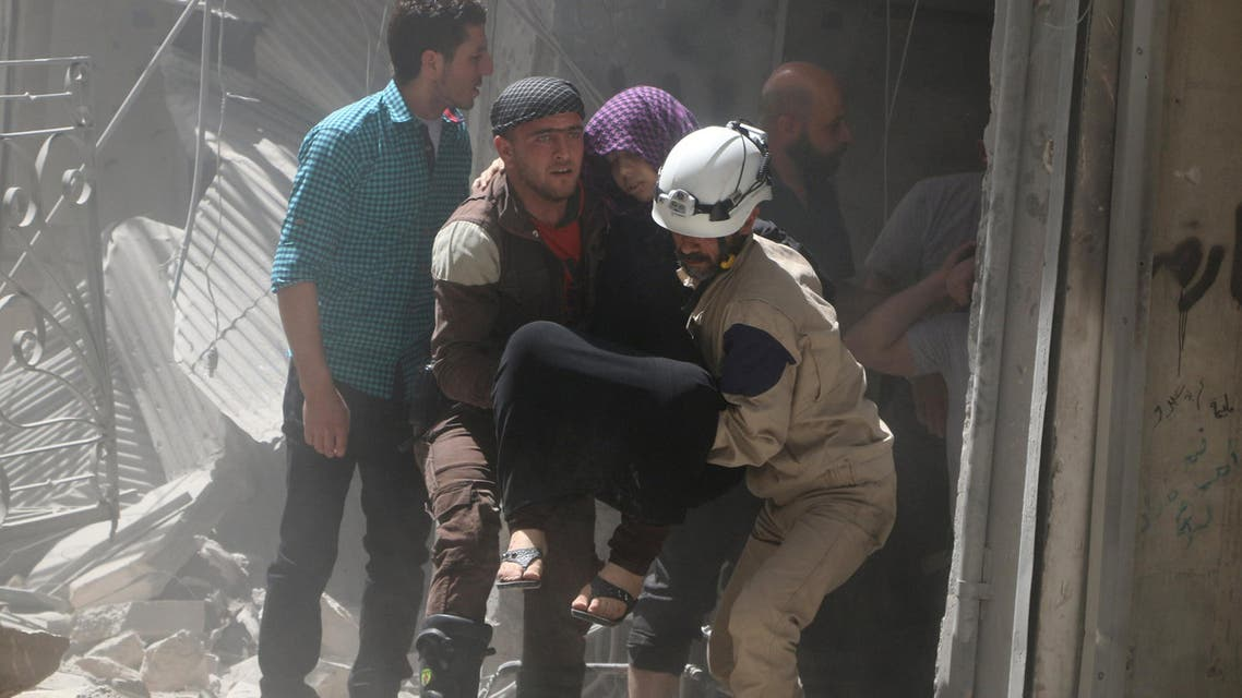 Civil defence members evacuate a woman from a damaged building after airstrikes in the rebel held area of old Aleppo, Syria April 22, 2016. Reuters