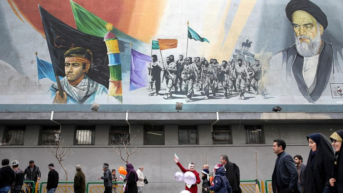 Iranians attend a rally commemorating the 37th anniversary of Islamic revolution under a mural of the late Iranian revolutionary founder Ayatollah Khomeini and Basij paramilitary force, in Tehran, Iran, Thursday, Feb. 11, 2016. The nationwide rallies commemorate Feb. 11, 1979, when followers of Ayatollah Khomeini ousted U.S.-backed Shah Mohammad Reza Pahlavi. (AP Photo/Ebrahim Noroozi)