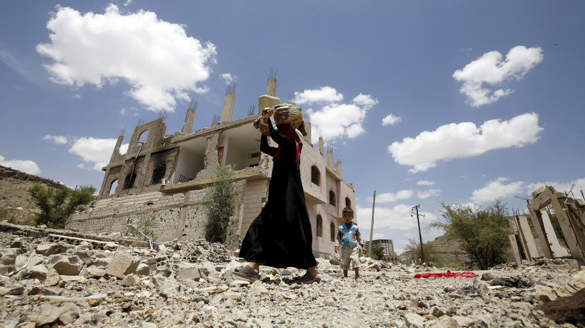 A woman and a boy walk past the ruins of buildings destroyed in Saudi-led air strikes in Yemen's capital Sanaa, September 13, 2015.