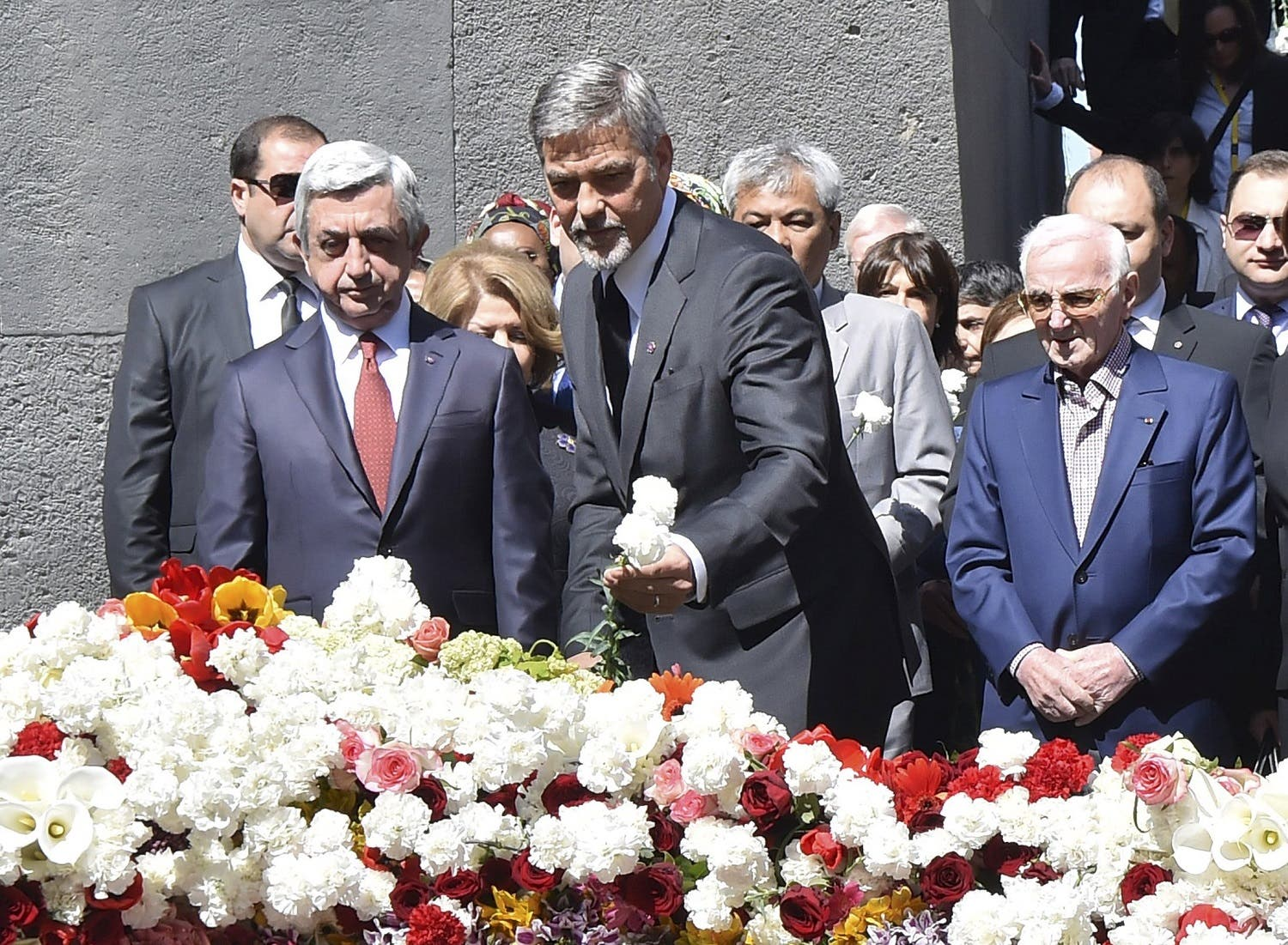Armenia's President Sargsyan, actor Clooney and singer Aznavour attend a flower-laying ceremony at the Tsitsernakaberd Armenian Genocide Memorial Museum in Yerevan. (Reuters)
