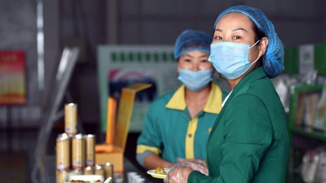 Workers serve samples of halal food products produced at the Sai Wai Xiang Halal Foodstuff Co in Qingtongxia, northern China's Ningxia province. (AFP)