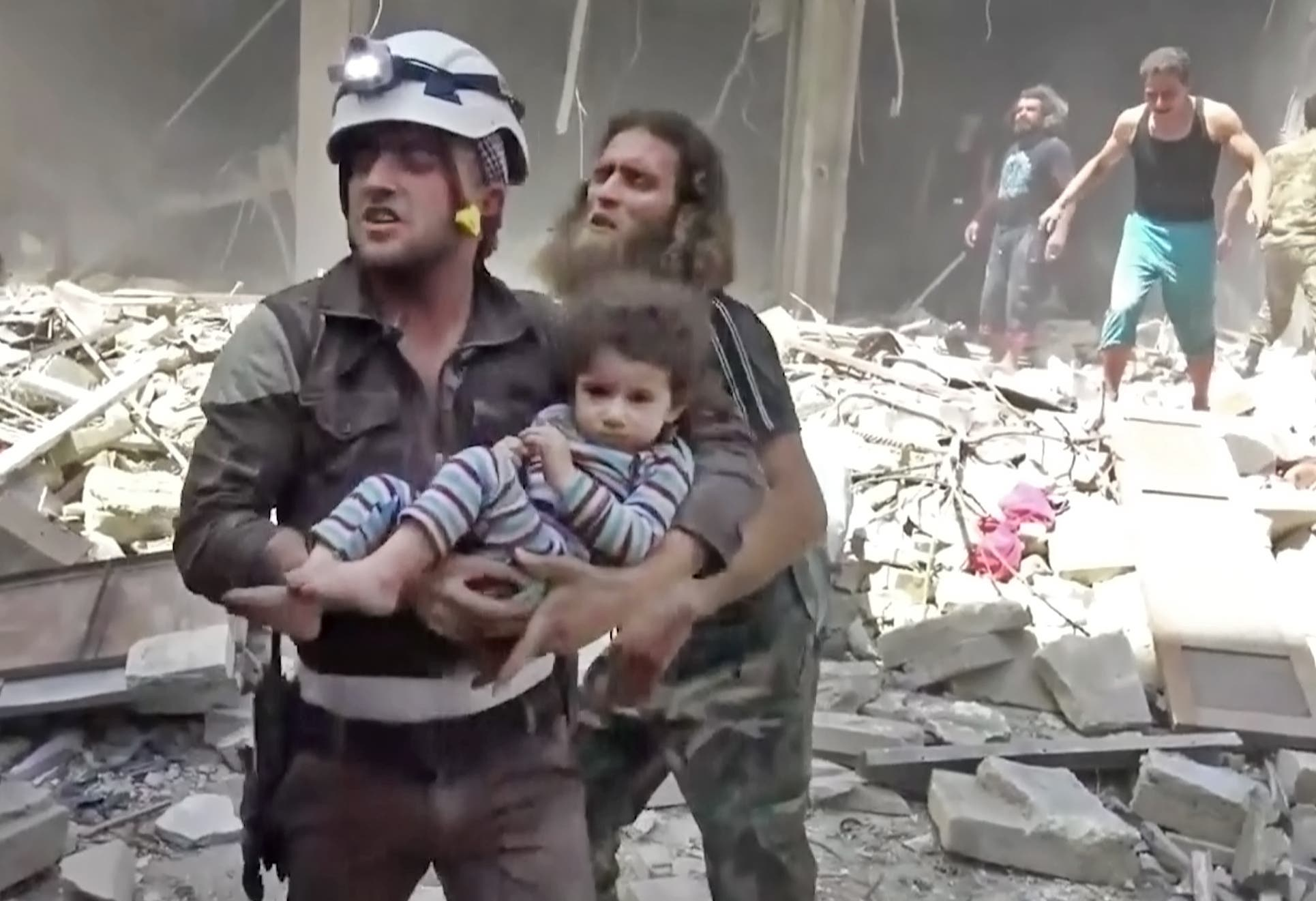In this image made from video and posted online from Validated UGC, a Civil Defense worker carries a child after airstrikes hit Aleppo, Syria, Thursday, April 28, 2016. (AP)