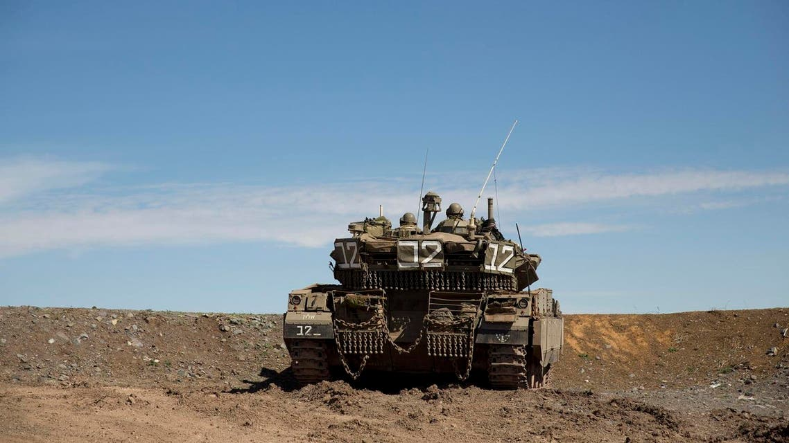 Israeli soldiers watch for their tank at the Druze village of Khader in Syria from the Israeli controlled Golan Heights, on the border with Syria, Thursday, Feb. 18, 2016. (AP Photo/Ariel Schalit)