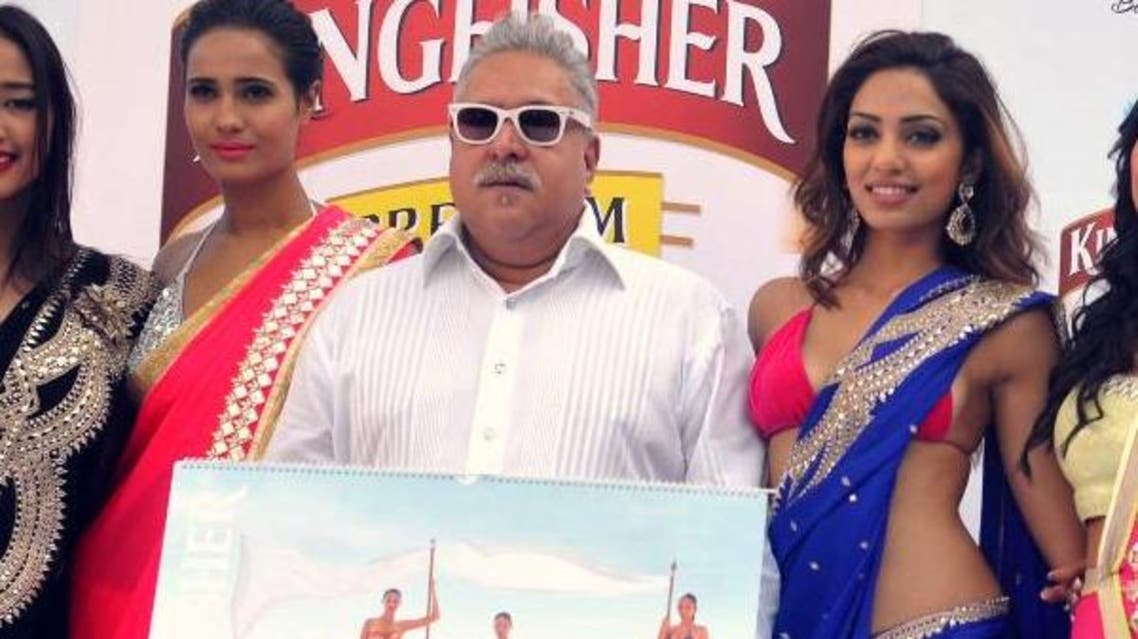 Indian UB Group chairman Vijay Mallya (C, in white) poses with models during the launch of the Kingfisher 2014 calendar in Mumbai on December 21, 2013. (AFP)