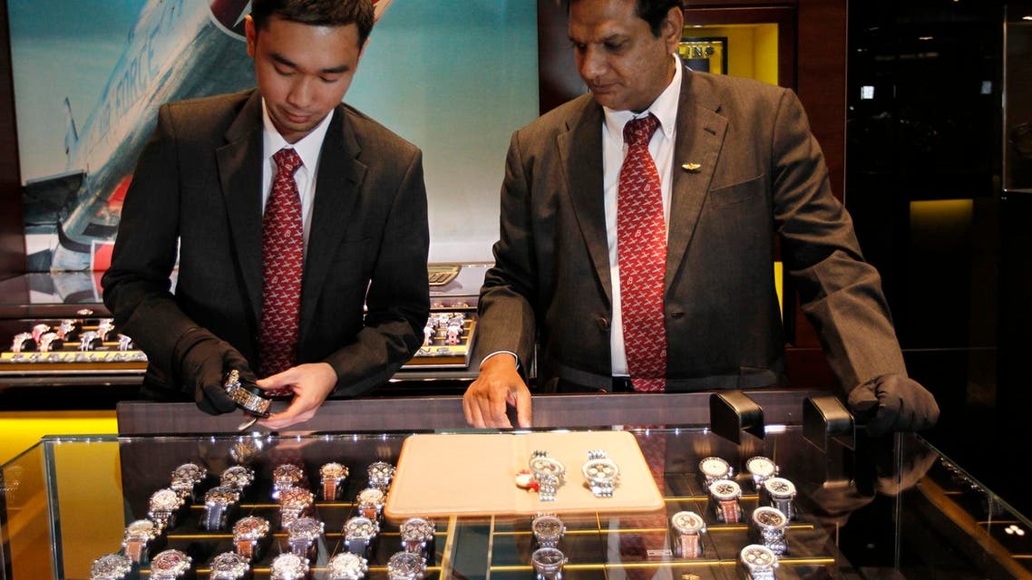 Salesmen show watches to customers at a Breitling watch store at the shopping centre Mall of the Emirates in Dubai, January 11, 2012.