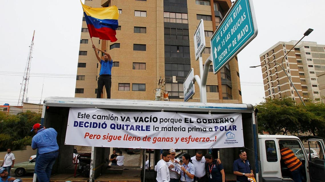 """Empresas Polar workers take part in a protest in Maracaibo, in the state of Zulia, Venezuela, April 29, 2016. The placard reads """"This truck is empty because the government decided to take the raw material to Polar. But still full of desire and effort!"""". REUTERS"""