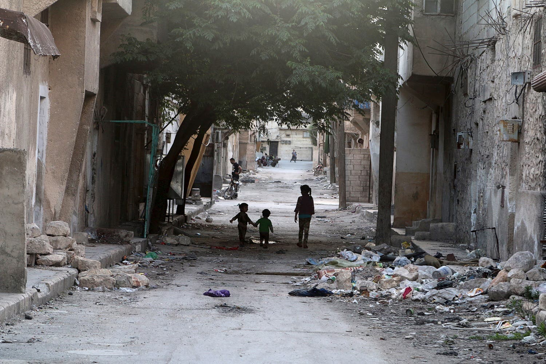 Children walk near garbage in al-Jazmati neighbourhood of Aleppo, Syria April 22, 2016. (Reuters)
