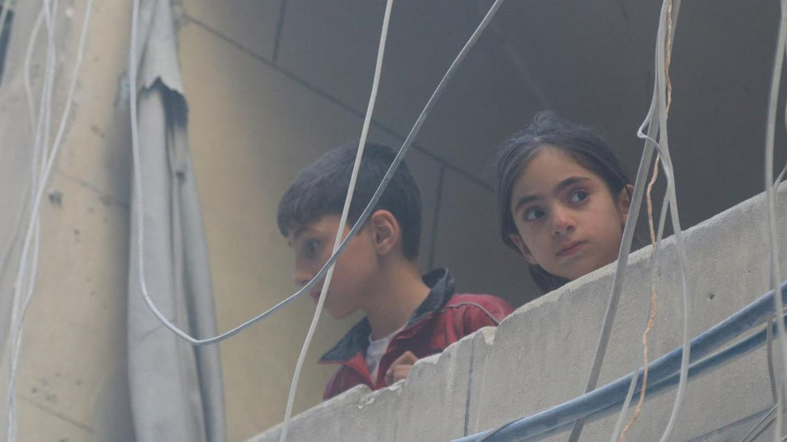 Children look out from a balcony at a site hit by airstrikes, in the rebel-held area of Aleppo's Bustan al-Qasr, Syria April 29, 2016. REUTERS