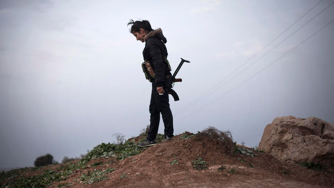 In this Sunday, March. 3, 2013 file photo, a Kurdish female member of the Popular Protection Units stands guard at a checkpoint near the northeastern city of Qamishli, Syria. AP
