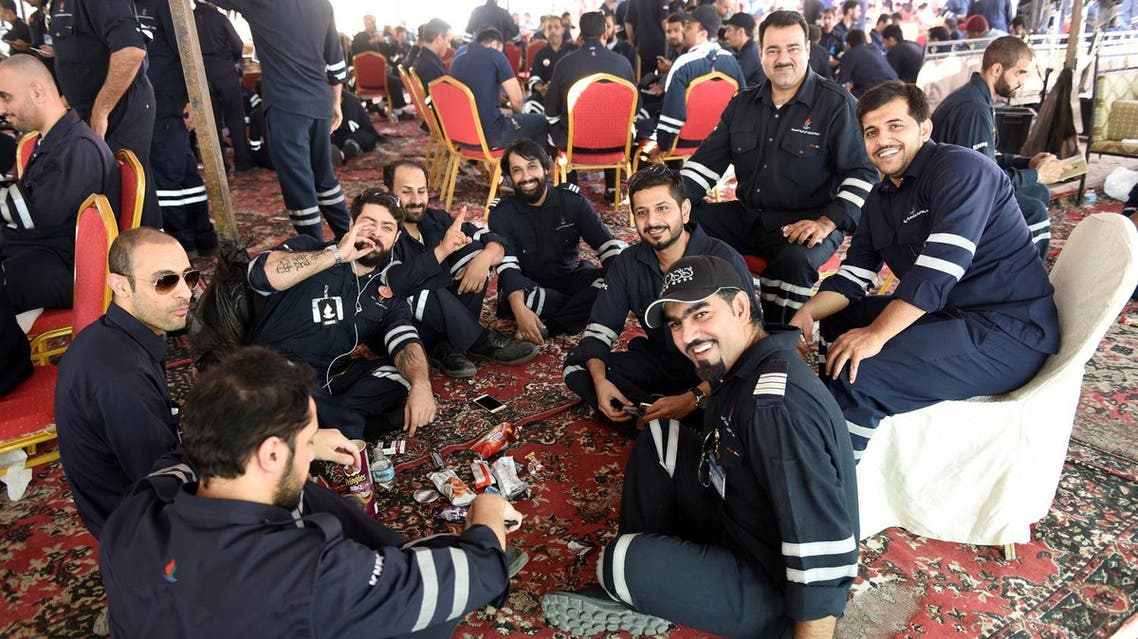 Kuwaiti oil sector employees sit in a shaded area on the first day of an official strike called by the Oil and Petrochemical Industries Workers Union over public sector pay reforms, in Ahmadi, Kuwait April 17, 2016. REUTERS