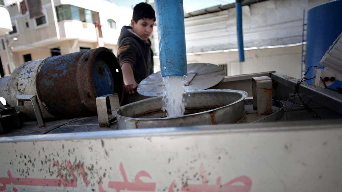 In this Thursday, April 14, 2016 photo, A Palestinian man fills tankers with drinking water for sale at a drinking water station in Gaza City. (AP)