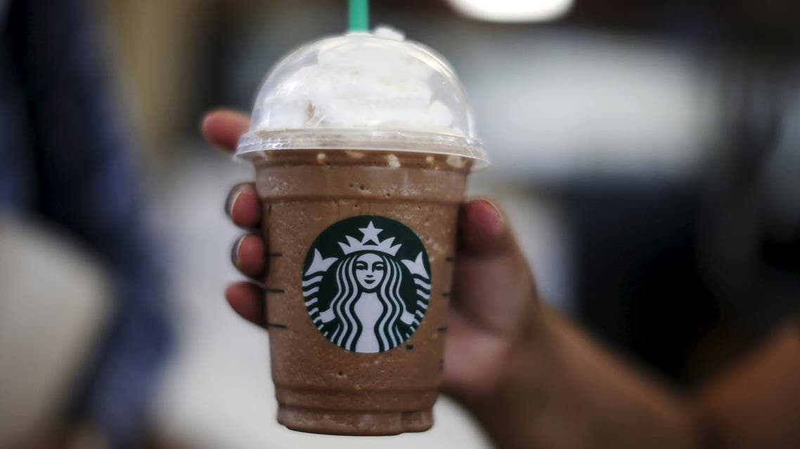 A woman holds a Frappuccino at a Starbucks store inside the Tom Bradley terminal at LAX airport in Los Angeles, California, United States, October 27, 2015. tarbucks Corp brewed up another quarter of strong sales and profit growth, but its shares fell more than 3 percent after the richly valued cafe chain's 2016 forecast offered little upside to Wall Street's target. Starbucks said on Thursday global sales at cafes open at least 13 months were up 8 percent in the fourth quarter ended Sept. 27, beating than the 6.9 percent rise expected by analysts polled by research firm Consensus Metrix. Picture taken October 27, 2015. REUTERS