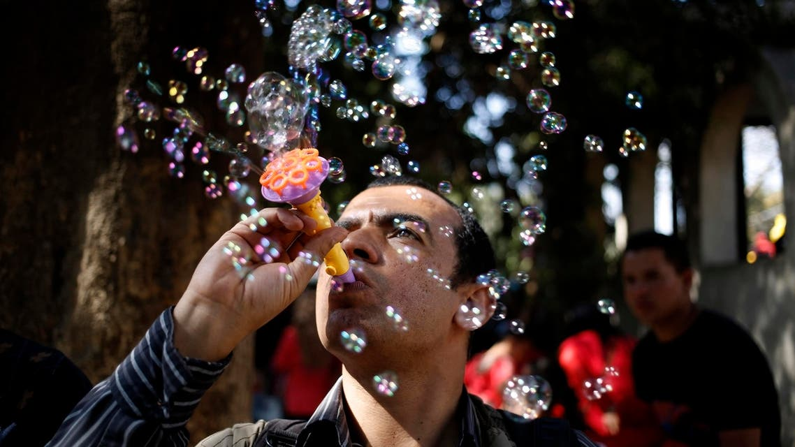"""An Egyptian man blows bubbles at the Giza Zoo, as the country marks Sham el-Nessim, or """"smelling the breeze,"""" in Giza, Egypt AP"""