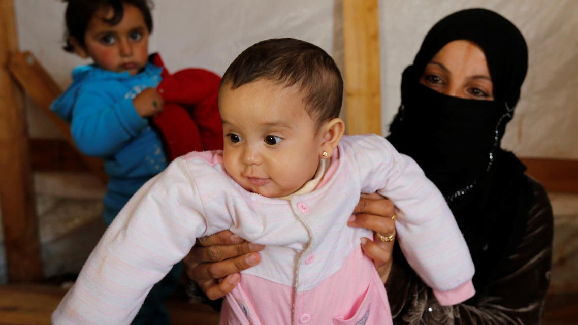 Syrian refugee Asheqa holds her unregistered baby daughter Nour inside a tent at a refugee camp near the town of Baalbek in LebanonÕs Bekaa valley, March 3, 2016. (Reuters)