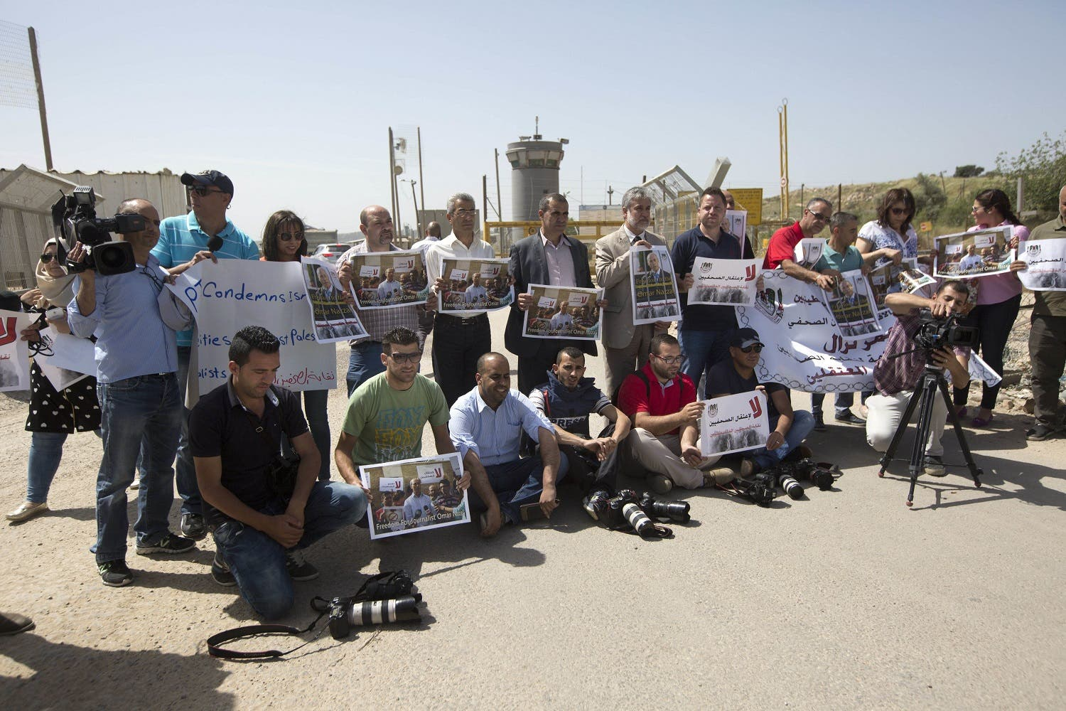 Palestinian journalists hold banners during a protest calling for the release of Palestinian journalist Omar Nazzal, who was arrested by Israeli authorities over the weekend, outside Ofer military prison near the West Bank city of Ramallah, Tuesday, April 26, 2016. (AP)