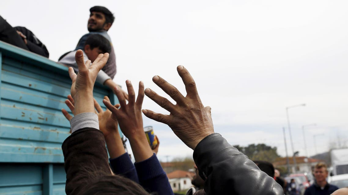Migrants and refugees reach out to get humanitarian aid at a makeshift camp at the Greek-Macedonian border near the village of Idomeni, Greece, March 26, 2016. (Reuters)