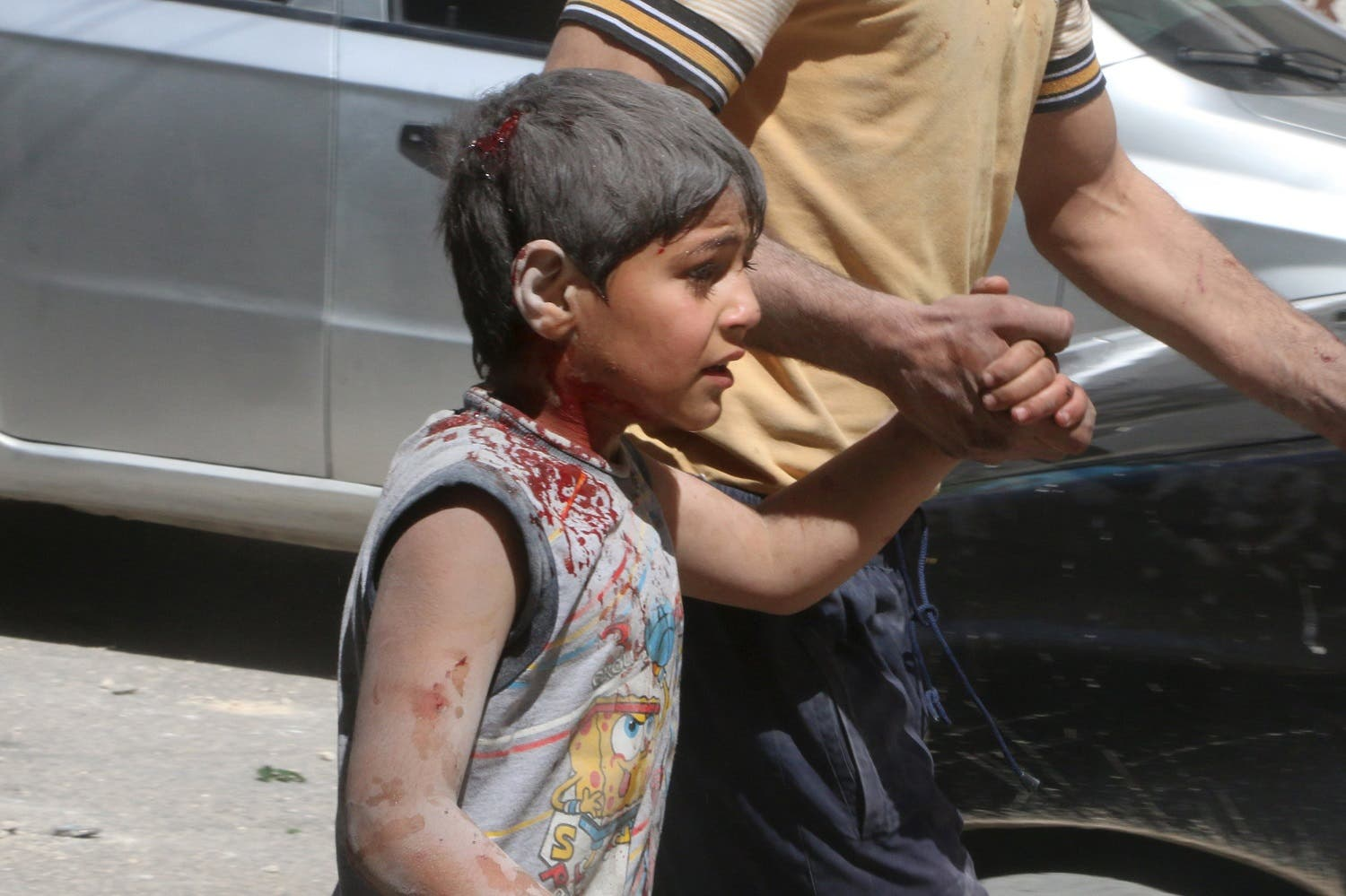 A man walks as he holds the hand of an injured boy after an airstrike in the rebel held area of old Aleppo, Syria April 22, 2016. (Reuters)