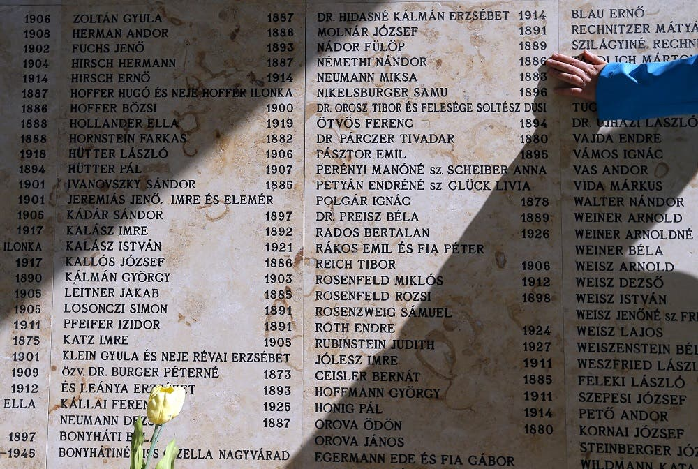 A woman touches a wall with names of Holocaust victims during a funeral of the remains of Holocaust victims in the Jewish cemetery in Budapest, Hungary April 15, 2016. (Reuters)