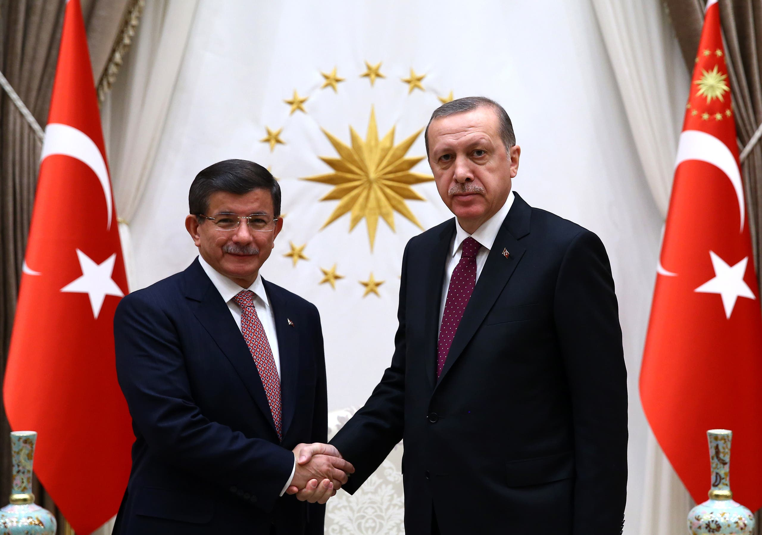 Turkey's Prime Minister Ahmet Davutoglu left, and President Recep Tayyip Erdogan shake hands before a meeting in Ankara, Turkey, Tuesday, Nov. 17, 2015. (AP)