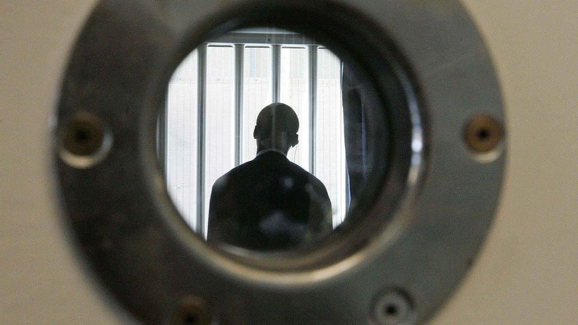 A security guard is seen through a small security window, in a room in the long-term wing at the new Colnbrook Immigration Removal Centre near London's Heathrow Airport, Thursday Sept. 16, 2004. AP