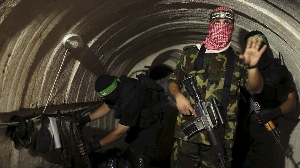 A Palestinian fighter from the Izz el-Deen al-Qassam Brigades, the armed wing of the Hamas movement, gestures inside an underground tunnel in Gaza (Reuters)