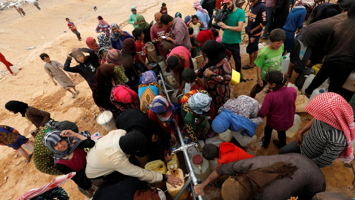 Syrian refugees stuck between the Jordanian and Syrian borders waiting to cross into Jordan, collect water, after a group of them crossed into Jordanian territory, east of the capital Amman, May 4, 2016. (Reuters)
