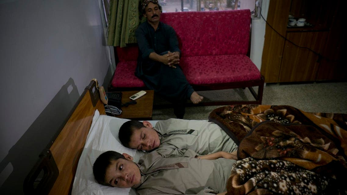 In this photo taken on Thursday, May 5, 2016, Abdul Rasheed, 9, front, and Shoaib Ahmed, 13, lie in a bed at a hospital in Islamabad, Pakistan. The boys are normal active children during the day. But once the sun goes down, they both lapse into a vegetative state — unable to move or talk. Dr. Javed Akram, told The Associated Press on Thursday that he had no idea what was causing the symptoms. (AP Photo/B.K. Bangash)