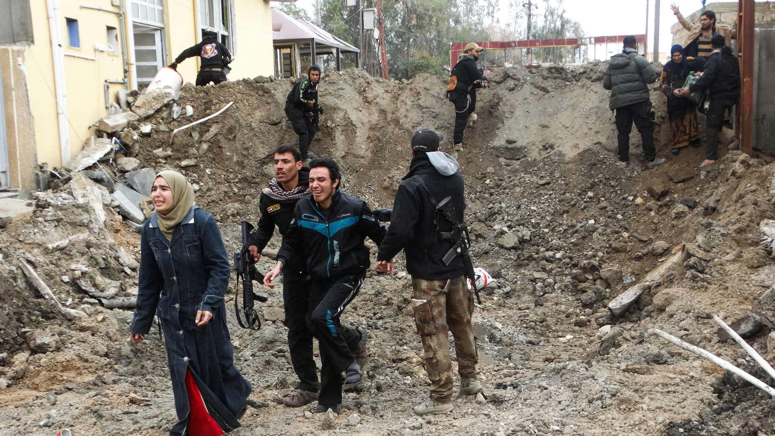 Iraqi security forces and Sunni tribal fighters help trapped civilians cross out of neighborhoods under Islamic State group control in Ramadi in this Jan. 4, 2016, file photo. ap