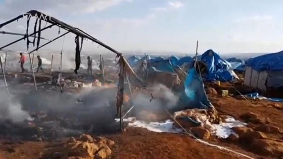 People walk though burnt tents at a camp for internally displaced people near Sarmada in Syria's Idlib province in this undated still image taken from video on May 6, 2016. Social Media