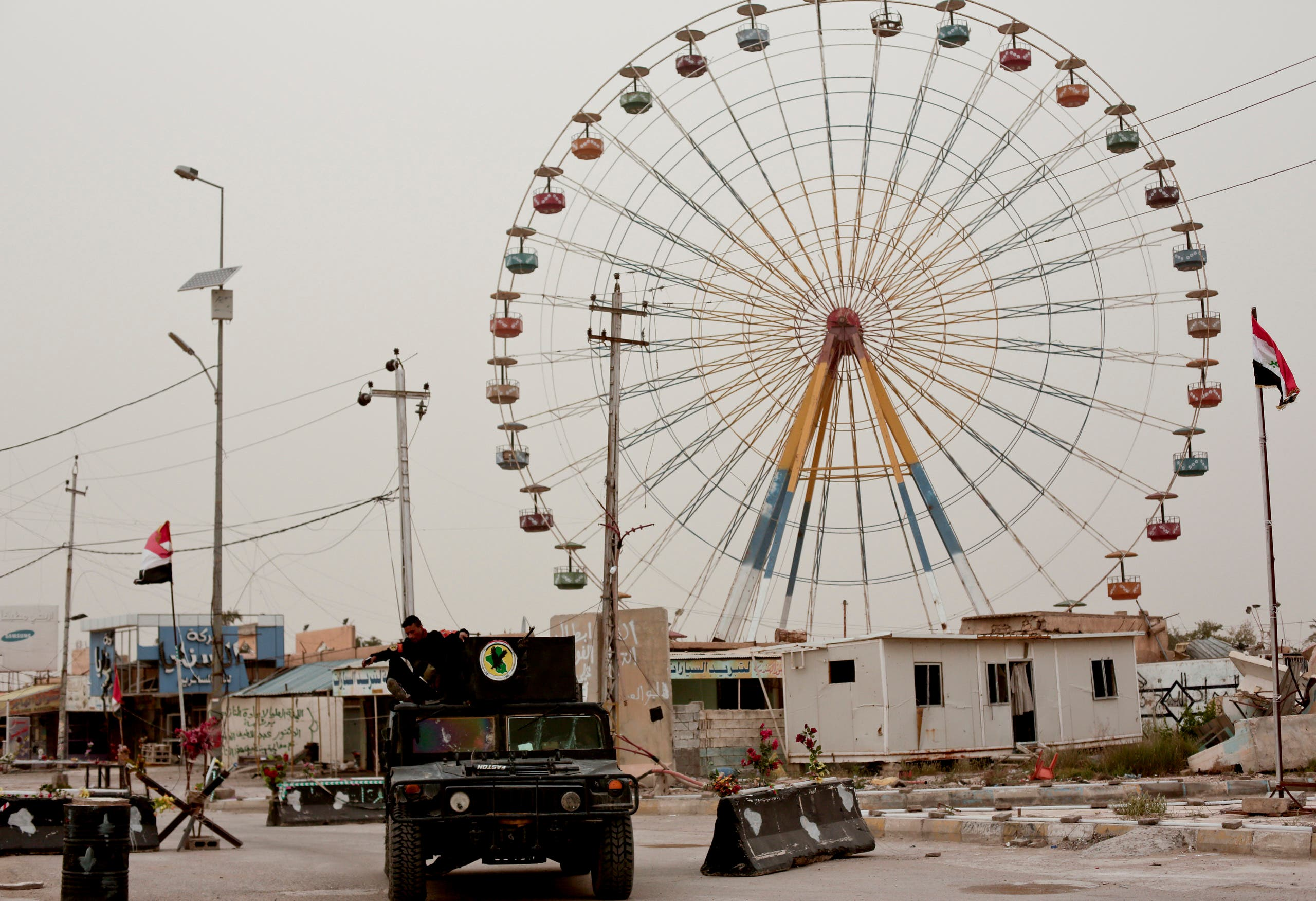 Iraqi counterterrorism forces drive past a ferris wheel in a central district of Ramadi on March 20, 2016. AP