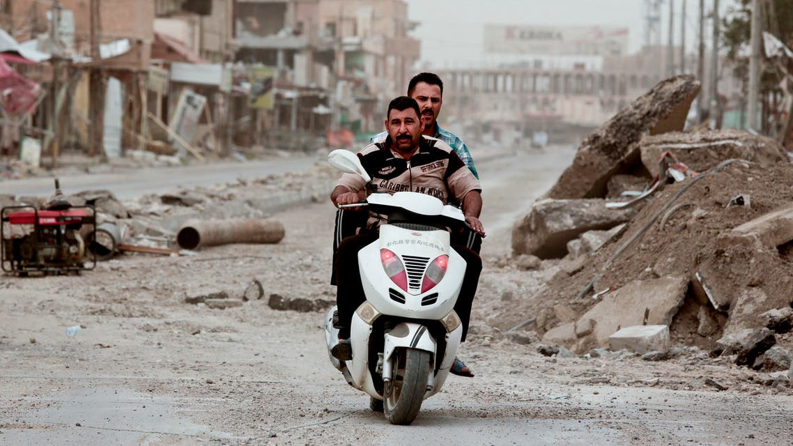Policemen ride a motorbike near Haji Ziad Square in the city of Ramadi, Iraq, on March 20, 2016, passing rubble that remains weeks after government forces retook the city from isis AP