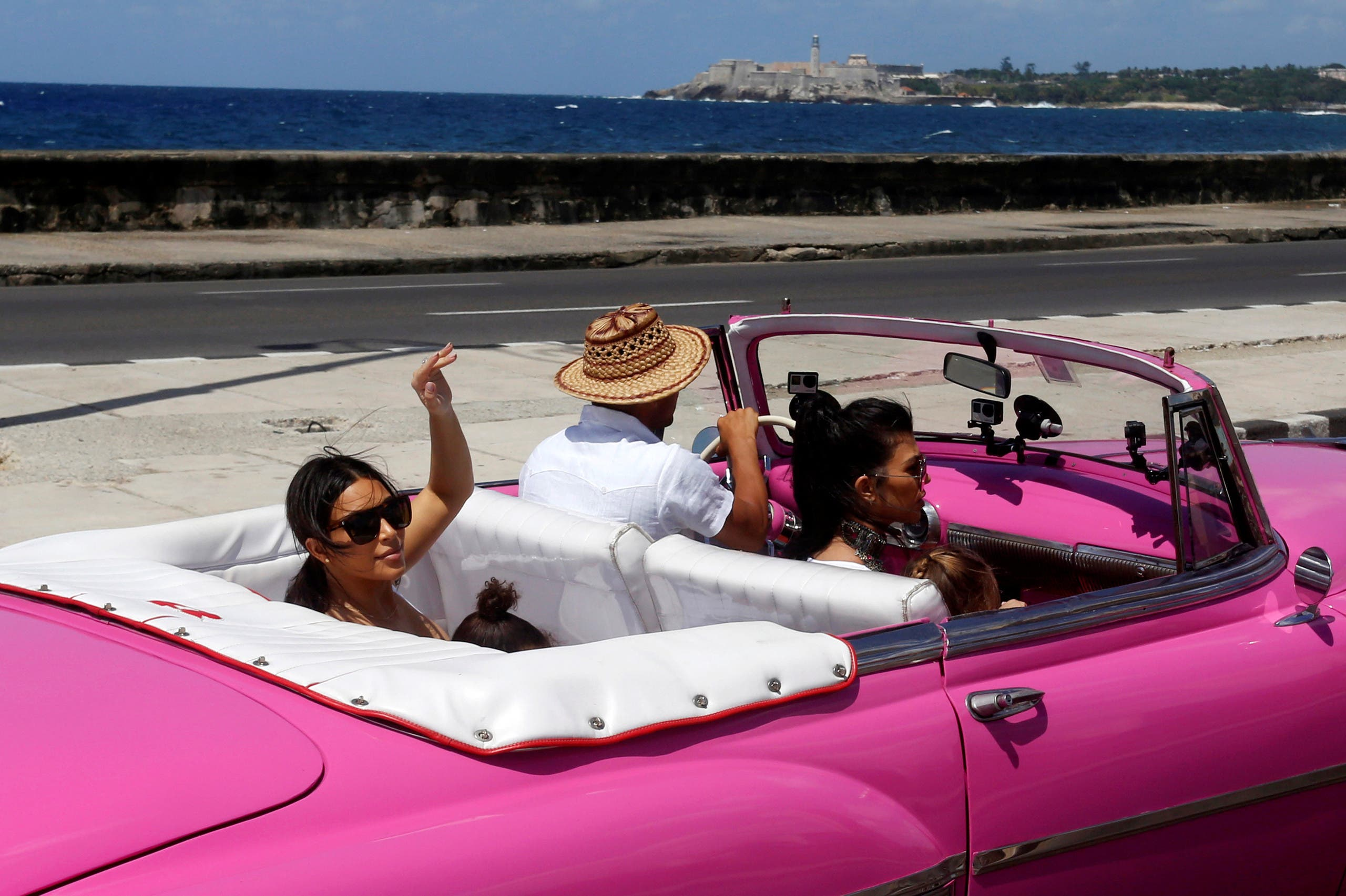 Kim Kardashian waves from the backseat of a vintage car at the seafront Malecon in Havana, Cuba, May 5, 2016. (Reuters)