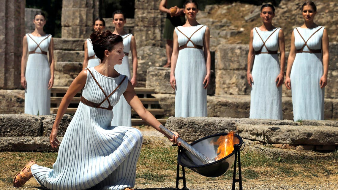 Greek actress Katerina Lehou , playing the role of High Priestess, lights a torch from the sun's rays reflected in a parabolic mirror during the dress rehearsal for the Olympic flame lighting ceremony for the Rio 2016 Olympic Games at the site of ancient Olympia in Greece, April 20, 2016. (Reuters)