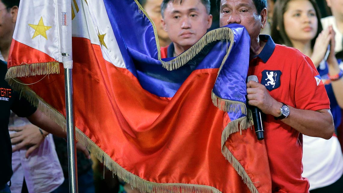 Philippine presidential race front-runner Davao city mayor Rodrigo Duterte kisses the Philippine flag during his final campaign rally in Manila, Philippines on Saturday, May 7, 2016. A bruising presidential campaign drew to a close in the Philippines Saturday with a last-minute attempt by the president to unify candidates against a front running mayor perceived as a threat to democracy virtually collapsing. (AP Photo/Aaron Favila)