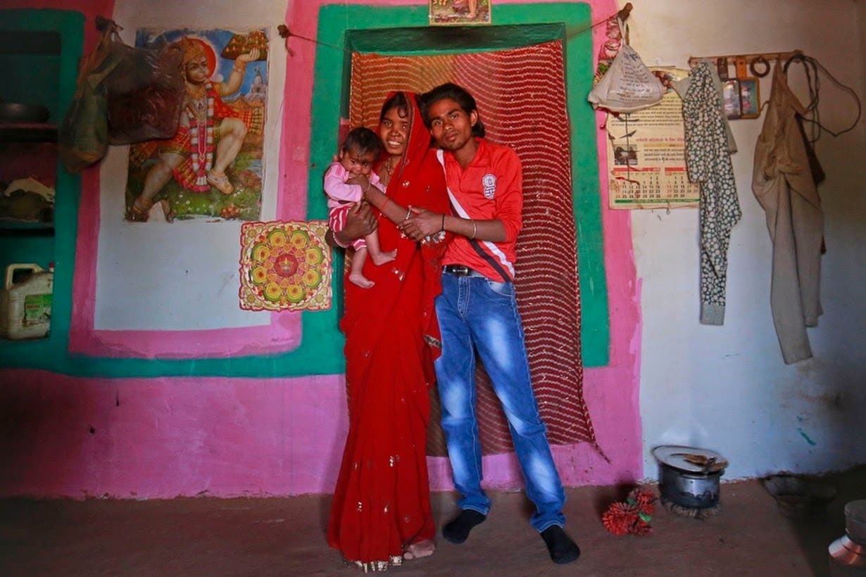 Krishna, 14, poses with her four-month-old baby Alok and husband Kishan Gopal, 16, inside the living room of their house in a village near Baran, located in the northwestern state of Rajasthan. (File photo: Reuters)