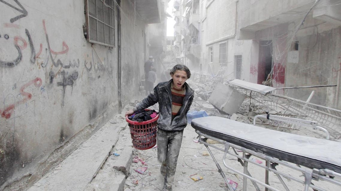 A boy carries his belongings at a site hit by what activists said was a barrel bomb dropped by forces loyal to Syria's President Bashar al-Assad in Aleppo's al-Fardous district. (Reuters)