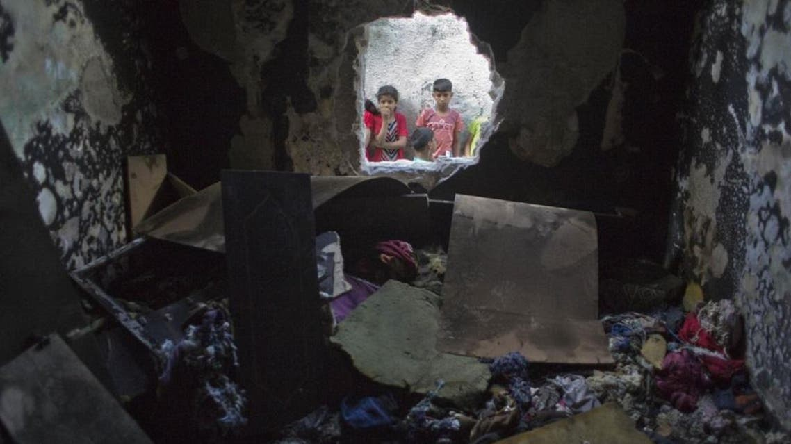 Palestinian children look through a hole in a wall at a burned bedroom where three children were killed by candle sparked on their family house in the Shati refugee camp in Gaza City, Saturday, May 7, 2016. Three Palestinian children have been killed in a Gaza house fire started by a candle, sparking internal finger-pointing over the coastal territory's lingering power crisis. (AP)