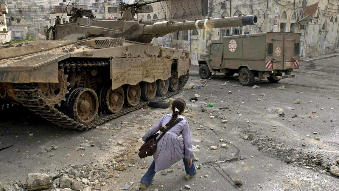 A Palestinian schoolgirl walks carefully next to an Israeli tank during clashes near her school in the northern West Bank town of Nablus, in this April 19, 2003 photo.