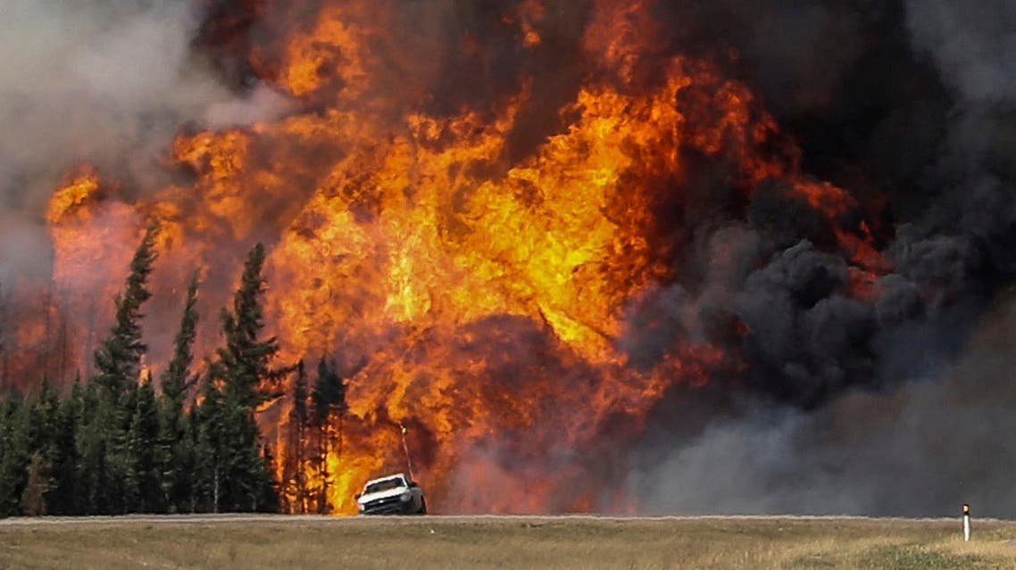 Smoke and flames from the wildfires erupt behind a car on the highway near Fort McMurray, Alberta, Canada, May 7, 2016. REUTERS