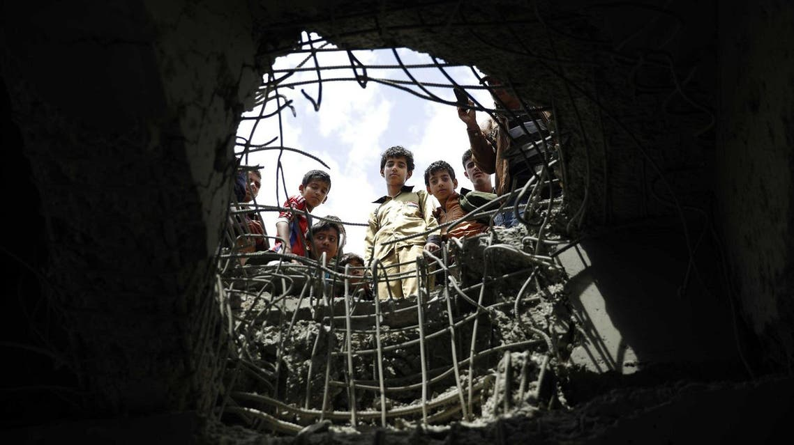 Boys look through a hole made by a Saudi-led airstrike on a bridge in Sanaa, Yemen, Wednesday, March 23, 2016. Yemen has been left fragmented by war pitting Shiite Houthi rebels and military units loyal to a former president against a U.S.-backed, Saudi-led coalition supporting the internationally recognized government. (AP Photo/Hani Mohammed)