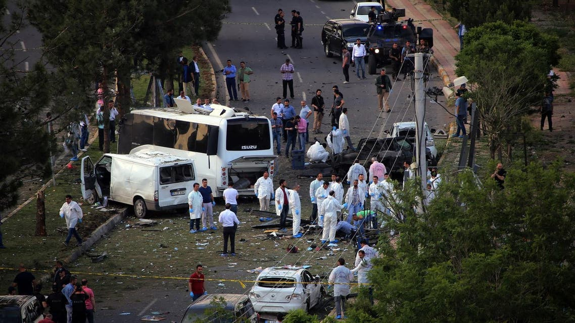Security officers and medics work at the explosion site after a car bomb struck a bus in Diyarbakir, Turkey, Tuesday, May 10, 2016. Turkey's state-run news agency says a car bomb attack targeting a bus carrying police officers in the mainly Kurdish city of Diyarbakir has killed at least three people. Anadolu Agency says at least 22 other people were wounded in the attack in Diyarbakir's Baglar neighborhood. The agency says the attack was carried out by the outlawed Kurdistan Workers' Party, or PKK. (AP Photo/Mahmut Bozarslan)