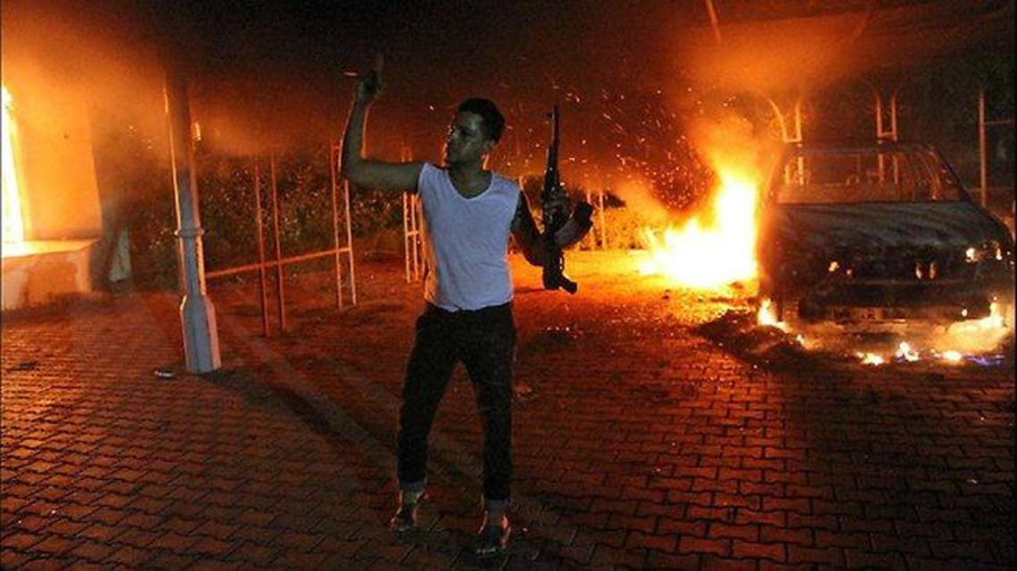 An armed man waves his rifle as buildings and cars are engulfed in flames after being set on fire inside the US consulate compound in Benghazi. (AFP)