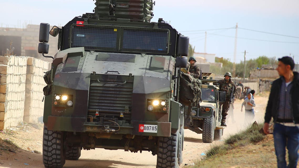 Tunisian soldiers ride armored vehicles as they search for attackers still at large in the outskirts of Ben Guerdane, southern Tunisia, Tuesday, March 8, 2016. (AP Photo)