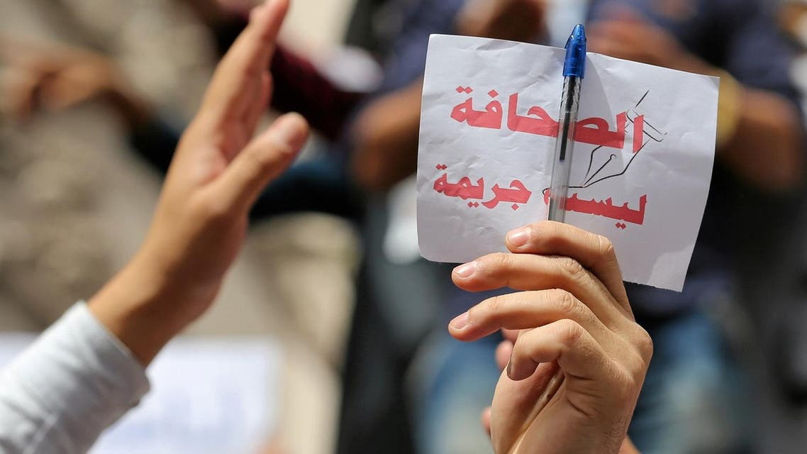 Journalist holds up a sign, which reads: ''Journalism is not a crime'', during a protest against restrictions on the press and to demand the release of detained journalists, in front of the Press Syndicate in Cairo. (File photo: Reuters)