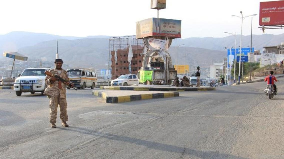 A picture taken on May 3, 2016 shows a Yemeni security forces member patrolling a street with a banner hung by Al-Qaeda militants announcing Islamists' orders of streets seen behind him, in the Yemeni port of Mukalla. (File photo: AFP)