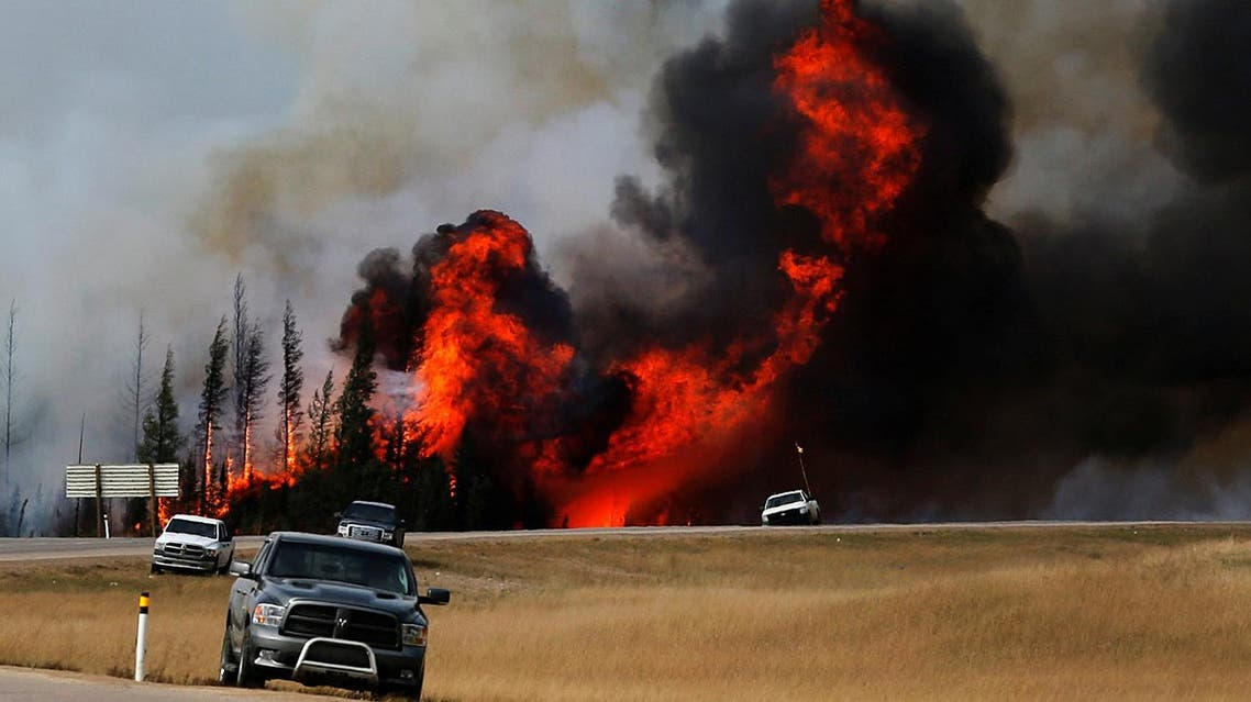 Smoke and flames from the wildfires erupt behind cars on the highway near Fort McMurray, Alberta, Canada, May 7, 2016. REUTERS