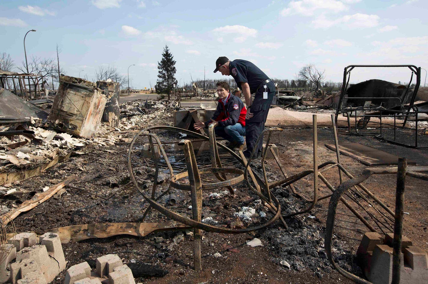 Prime Minister Justin Trudeau (L) and Fort McMurray Fire Chief Darby Allen look over the devastation after a wildfire during a visit to Fort McMurray, Alberta, Canada, May 13, 2016. REUTERS