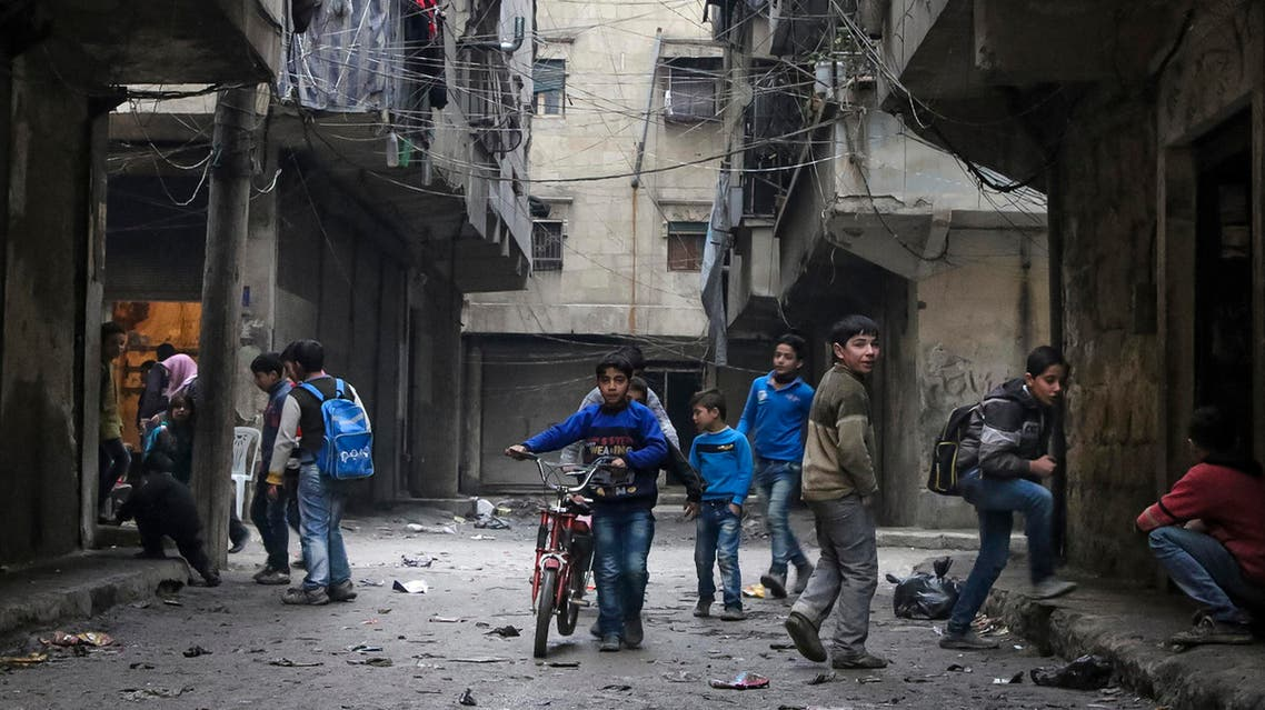 In this Thursday, Feb. 11, 2016 photo, school boys play in a street in Aleppo, Syria. The fighting around Syria's largest city of Aleppo has brought government forces closer to the Turkish border than at any point in recent years, routing rebels from key areas and creating a humanitarian disaster as tens of thousands of people flee. (Alexander Kots/Komsomolskaya Pravda via AP)